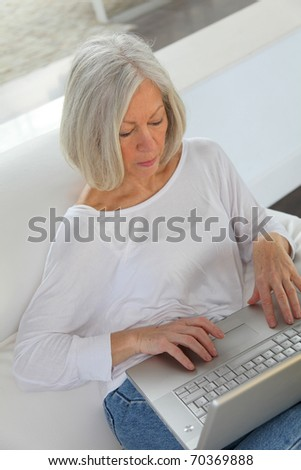 Senior woman surfing on internet at home