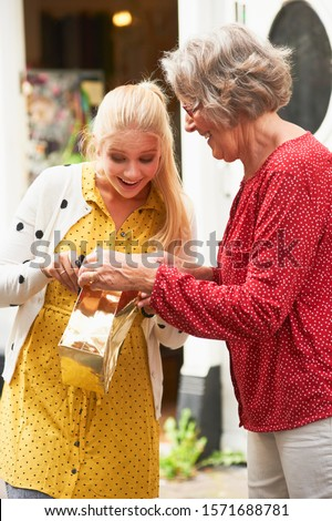 Senior woman surprising granddaughter with gift