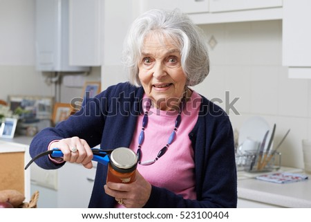 Senior Woman Taking Lid Off Jar With Kitchen Aid #523100404