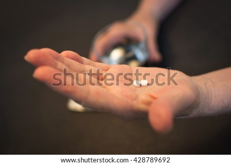 Senior woman taking pills with a glass of water.