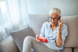 Senior woman talking on the phone and holding a pack of pills.  Woman refilling her medication prescription drugs online using smart phone technology app in her home