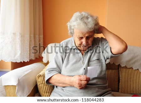 senior woman thinking while reading a note