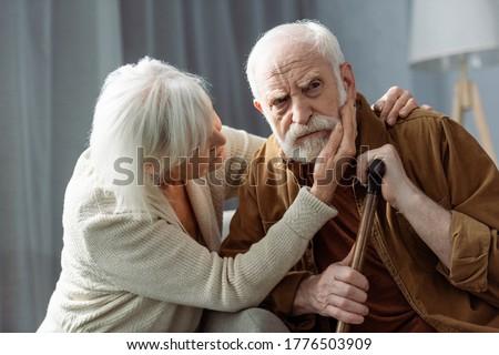 senior woman touching face and hugging husband sick on dementia Сток-фото ©