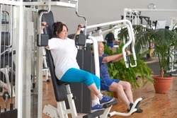Senior woman training on machine at gym. Elderly people exercising at fitness club. How to help seniors to stay active.