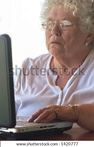 Senior woman trying hard to figure out the laptop.