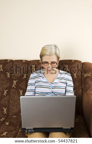 Senior woman using a laptop home and sitting on her couch