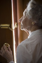 Senior woman using a security chain on front door