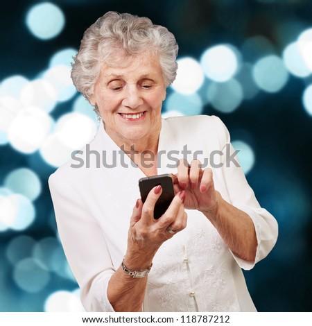 Senior woman using cellphone, illuminated