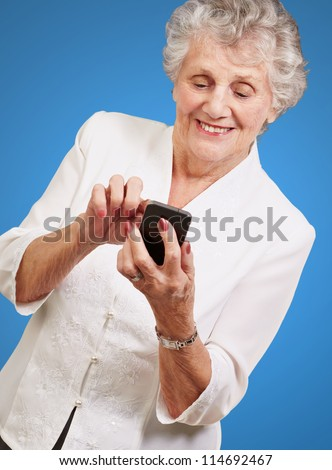 Senior woman using cellphone isolated on blue background