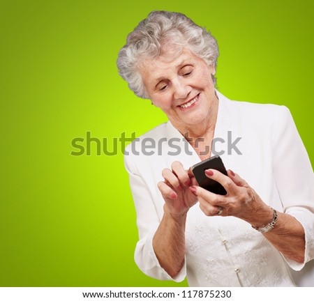Senior woman using cellphone isolated on green background