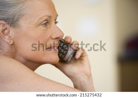 Senior woman using cordless phone, laughing, close-up, side view