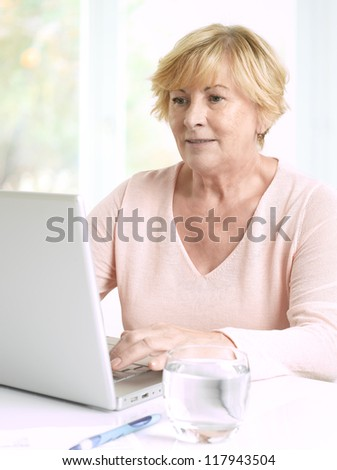 Senior woman using her laptop at home
