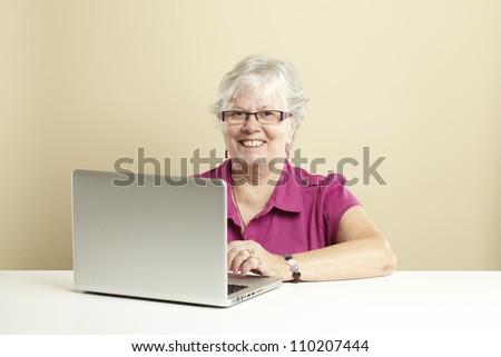 Senior woman using laptop whilst smiling
