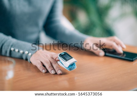 Photo of  Senior Woman Using Pulse Oximeter and Smart Phone, Measuring Oxygen Saturation