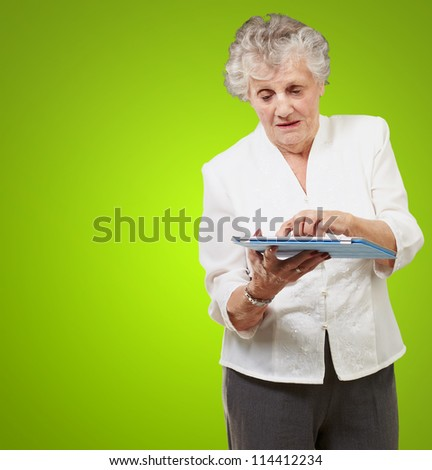 Senior woman using tablet isolated on green background