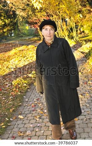 Senior woman walking alone in fall park