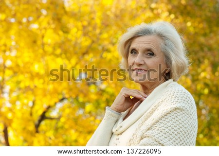 Senior woman walking in the park in autumn