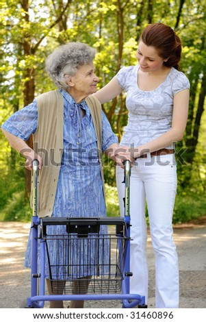 Senior  woman walking with the help of a granddaughter
