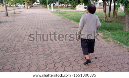 senior woman walking with walking stick in the park