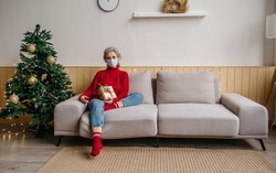 Senior woman wearing mask sitting on couch alone holding a gift in Christmas decorated room . Coronavirus self isolation and celebrate Christmas alone concept