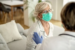 Senior woman wearing protective face mask while talking to her doctor who is visiting her at home during virus epidemic.