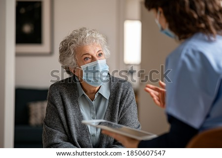 Senior woman wearing safety protective mask at home and talking to nurse. Back view of young doctor visiting old woman for routine health checkup during covid-19, coronavirus and flu outbreak. Photo stock ©