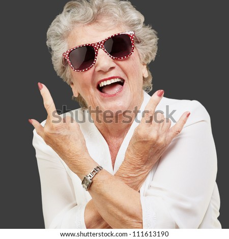 Senior woman wearing sunglasses doing funky action isolated on black background