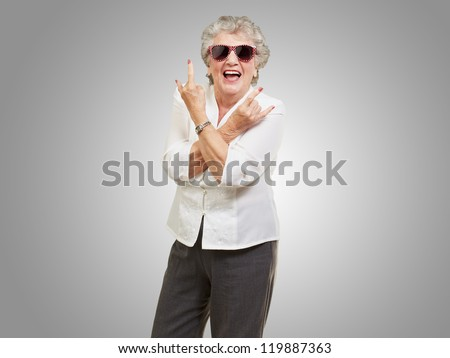 Senior woman wearing sunglasses doing funky action isolated on gray background
