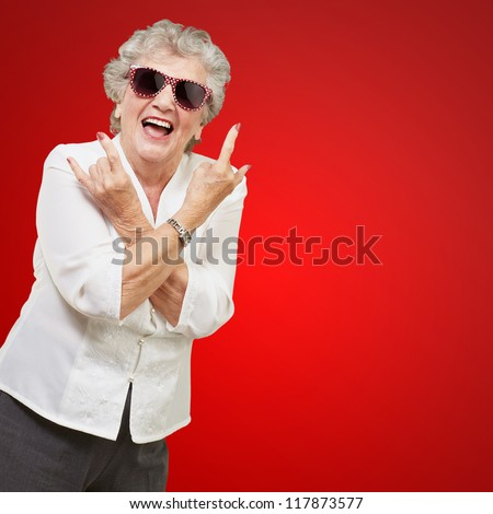 Senior woman wearing sunglasses doing funky action isolated on red background