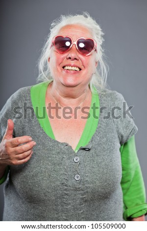 Senior woman wearing sunglasses with expressive face. Funny. Studio shot isolated on grey background.