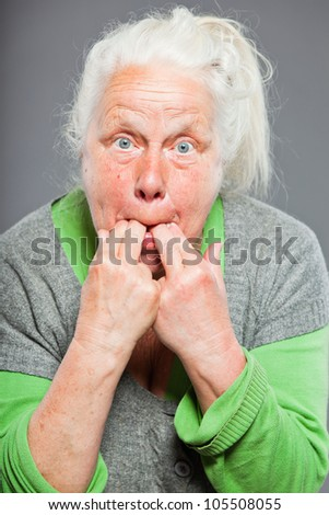 Senior woman whistling with her fingers. Acting young. Studio shot isolated on grey background.