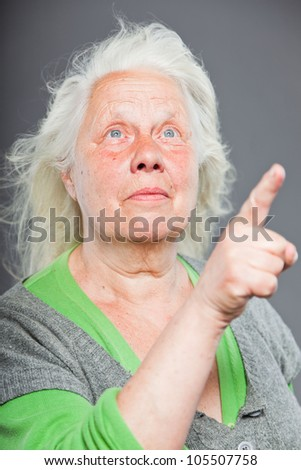 Senior woman white grey hair doing spiritual poses. Expressive face and hands. Studio shot isolated on grey background.