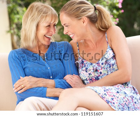 Senior Woman With Adult Daughter Relaxing On Sofa At Home - stock photo