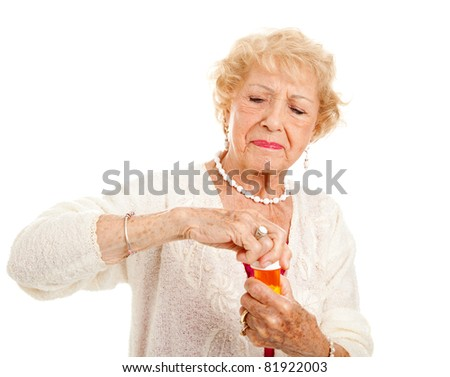 Senior woman with arthritis struggles to open a bottle of prescription medication.
