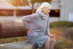 Senior woman with back pain having difficulty to get up from the bench