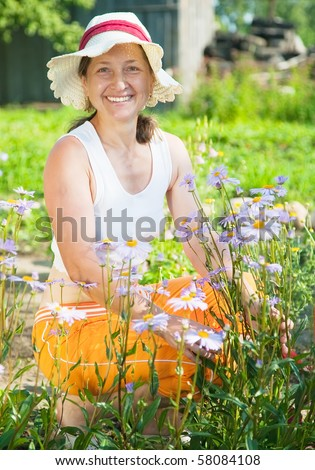senior woman with blue camomile im her garden