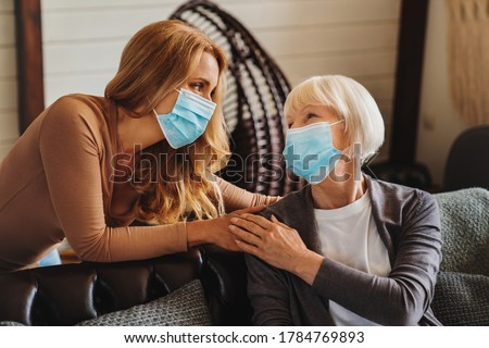 Senior woman with caring daughter at home. Females wearing medical masks.