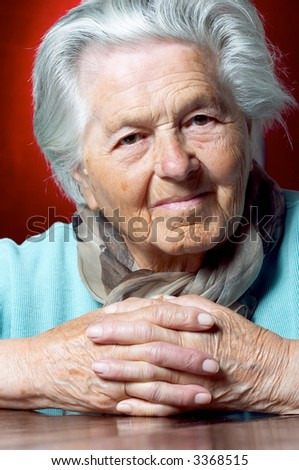 Senior woman with clasped hands looks at the camera