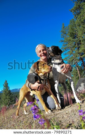 Senior woman with dogs on leash on dirt road