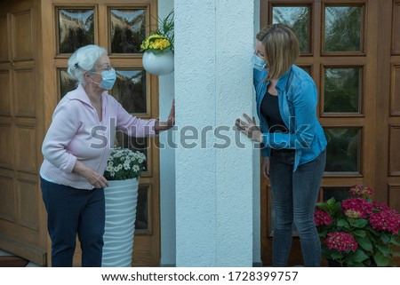 Senior woman with face mask in house quarantine talks to neighbor at safety distance