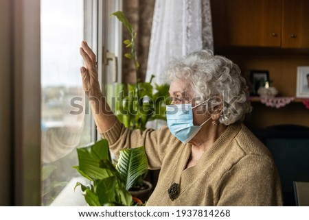 Senior woman with face mask looking out of window at home  Stockfoto ©