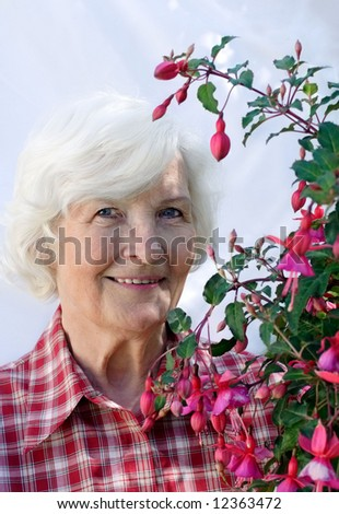 Senior woman with fuchsia flower plant