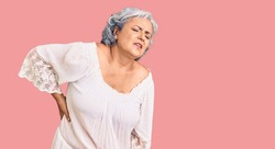 Senior woman with gray hair wearing bohemian style suffering of backache, touching back with hand, muscular pain
