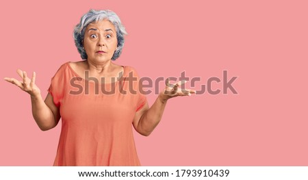 Senior woman with gray hair wearing orange tshirt clueless and confused expression with arms and hands raised. doubt concept.