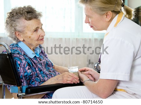 Senior woman with her home caregiver. - stock photo
