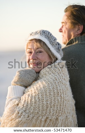 Senior woman with husband dressed in warm clothing - stock photo
