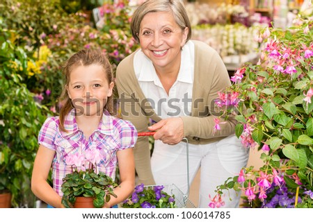 Senior woman with little girl shopping flowers at garden centre