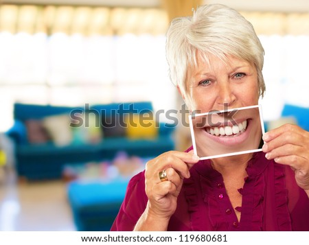Senior Woman With Magnifying Glass Showing Teeth, Indoor