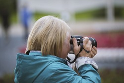 Senior woman with photo camera at summer day in park, outdoor, rear view