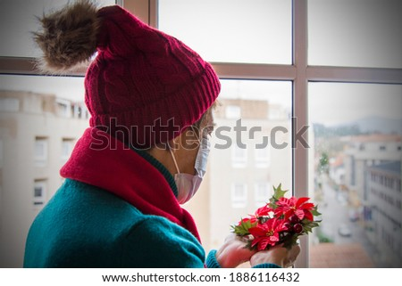 senior woman with protective face mask placing christmas decorations at christmas Foto stock ©